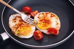Fried eggs in a pan with smoked paprika and fresh cherry tomatoes royalty free stock image