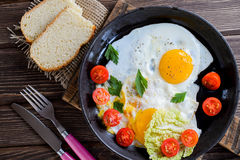 Fried eggs in pan with tomato, bread, pepper and parsley. On wooden background Royalty Free Stock Images