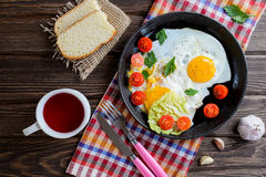 Fried eggs in pan with tomato, bread, pepper and parsley. On wooden background Stock Photo