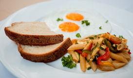 Fried eggs with pasta on the white plate Stock Photography