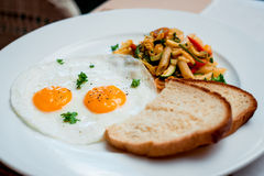 Fried eggs with pasta on the white plate Royalty Free Stock Photos