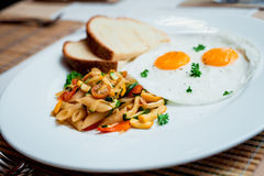 Fried eggs with pasta on the white plate Stock Image