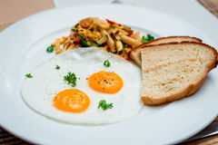 Fried eggs with pasta on the white plate Royalty Free Stock Photography