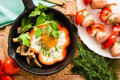Fried eggs in pepper in the pan and the sausages with peppers. On plate. Wooden table. Top view Royalty Free Stock Image