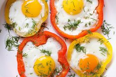 Fried eggs with peppers macro. horizontal top view Stock Images