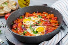 Fried eggs with pieces of pumpkin, red onions and tomatoes. Tasty breakfast stock photography