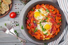 Fried eggs with pieces of pumpkin, red onions and tomatoes. Tasty breakfast. View from above royalty free stock photography