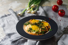 Fried eggs on the plate with cherry tomatoes, spices and green onions in rustic style. Nutritious organic breakfast Stock Image