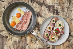 Fried Eggs and Pork Bacon Rashers in Teflon Frying Pan with Plate of Bacon, Cheese, Egg, Ham, and Tomato Sandwich on Old Wood Royalty Free Stock Photography