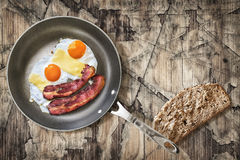 Fried Eggs and Pork Bacon Rashers in Teflon Frying Pan with slice of Integral Bread on Old Cracked Peeled Wooden Table Royalty Free Stock Photos