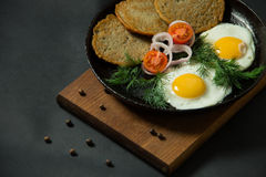 Fried eggs with potato pancakes and herbs in a pan on a black ba Stock Image