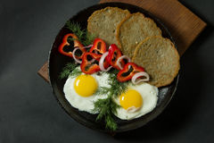 Fried eggs with potato pancakes and herbs in a pan on a black ba Royalty Free Stock Photos