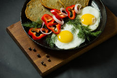 Fried eggs with potato pancakes and herbs in a pan on a black ba Royalty Free Stock Photography