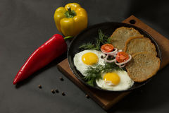 Fried eggs with potato pancakes and herbs in a pan on a black ba Stock Photo