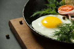 Fried eggs with potato pancakes and herbs in a pan on a black ba Stock Photos