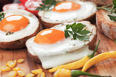 Fried eggs in potato shells. Fried chicken eggs in roasted potato shells served on wooden board Royalty Free Stock Image
