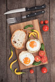 Fried eggs in potato shells. Fried chicken eggs in roasted potato shells served on wooden board Stock Photo