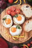 Fried eggs in potato shells. Fried chicken eggs in roasted potato shells served on wooden board Royalty Free Stock Photo