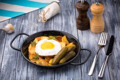 Fried eggs and potatoes in a frying pan with pickles on wooden background Stock Images
