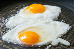 Fried eggs preparation Stock Photography
