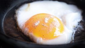 Fried eggs preparation on a frying pan. stock footage