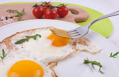 Fried eggs with rucola leaves and cherry tomatoes. Fried eggs with arugula leaves and cherry tomatoes Royalty Free Stock Images