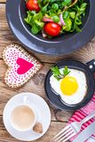 Fried eggs, salad and coffee for breakfast for Valentine`s Day royalty free stock photo