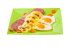 Fried eggs with salami on green plate Stock Photo