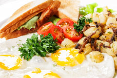 Fried eggs with sandwich and vegetables. Breakfast from fried eggs of fried potato with mushrooms and tomatoes Stock Photo