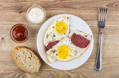 Fried eggs with sausage, bread, bowl with mayonnaise and ketchup Stock Photo