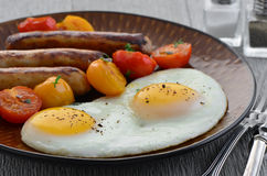 Fried eggs, sausage and cherry tomatoes Stock Photo