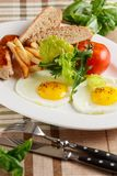 Fried eggs with sausage and fries Royalty Free Stock Photo