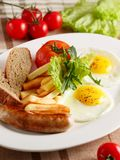 Fried eggs with sausage and fries Stock Image