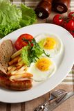 Fried eggs with sausage and fries Royalty Free Stock Images