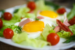Fried eggs with sausage and tomato Stock Photo