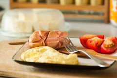 Fried eggs with sausage and tomato on the wooden table Stock Photography