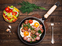 Fried eggs with sausage and tomatoes in frying pan served with s