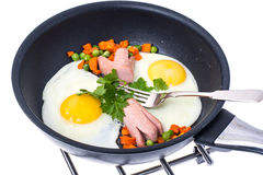 Fried eggs with sausage and vegetables in frying pan on white ba Stock Images