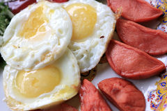 Fried eggs with sausages Stock Photos