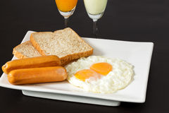 Fried eggs with sausages and bread on the white plate Royalty Free Stock Photography