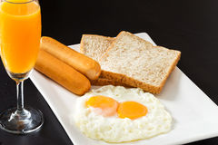 Fried eggs with sausages and bread on the white plate. In breakfast set Royalty Free Stock Images