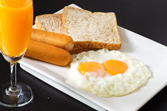 Fried eggs with sausages and bread on the white plate Royalty Free Stock Image
