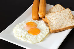 Fried eggs with sausages and bread on the white plate Stock Photos