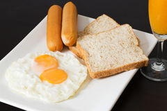 Fried eggs with sausages and bread on the white plate Royalty Free Stock Photos