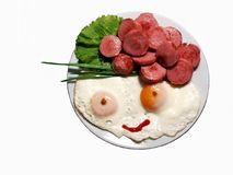 Fried eggs, Sausages, Lettuce. Closeup of two fried eggs forming smiling face with eyes and mouth drawn with ketchup, and hair and hat from fried sausages' royalty free stock photos