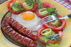Fried eggs and sausages in plate on  table Stock Photo
