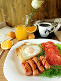 Fried eggs with sausages and tomatoes on a white plate surrounded by fruit Royalty Free Stock Photos