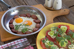 Fried eggs and sausages with vegetable salad on table Royalty Free Stock Images