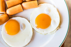 Fried eggs and sausages on white plate Royalty Free Stock Image