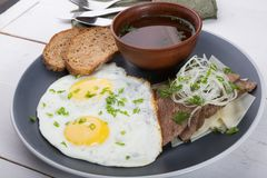 Fried eggs served with bread slices, meat slices and broth stock photography